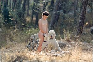 צילום ערום טבעי. אישה עם כלבים ביער בעירום.