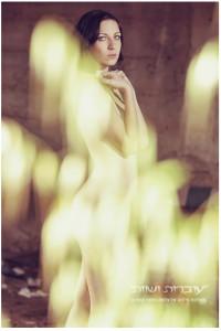 אישה ערומה מסתתרת אחרי עלים.