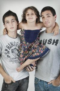 אחים גדולים מצטלמים עם אחותם בסטודיו